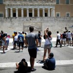 Tourists take pictures in front of the Unknown Soldier's Tomb with the parliament building seen in the background in Athens, Greece July 6, 2017. REUTERS/Alkis Konstantinidis